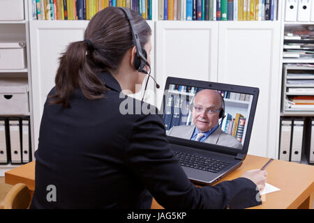 Woman with headset in front of her laptop writing something on a paper while making a live video call with a client - Stock Image