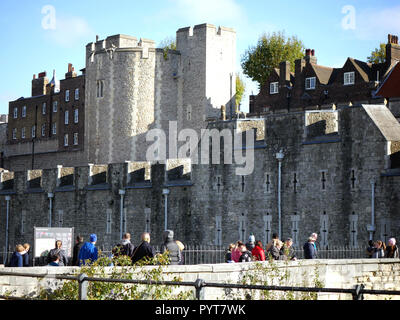 Tourists looking around the Tower of London checking information board - Stock Image