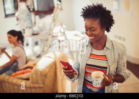 Woman drinking coffee and texting with smart phone - Stock Image