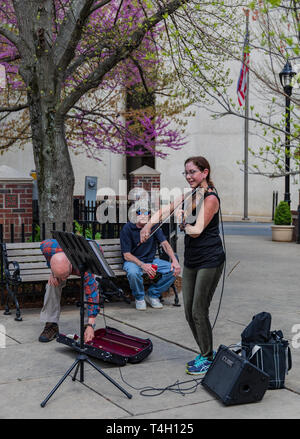 ASHEVILLE, NC, USA-4/11/19:  A woman smiling and busking in downtown, while a man puts money in her violin case, while another man sits and listens. - Stock Image