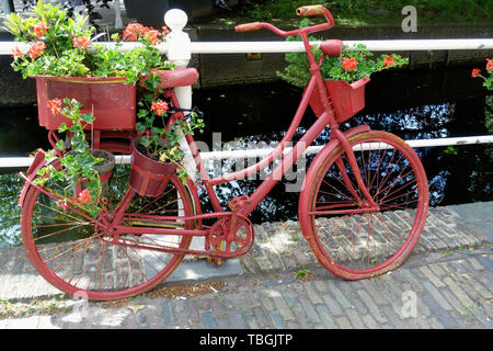 Old-fashioned Dutch city bike near a bridge over canal in the Old Town of Delft, Holland - Stock Image