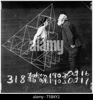 Alexander Graham Bell (1847-1922) facing his wife, Mabel Hubbard Gardiner Bell, who is standing in a tetrahedral kite, 1902 - Stock Image