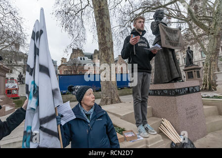 London, UK. 15th January 2019. An Earth Strike UK campaigner explains that this is the first of 4 international actions leading to a global General Strike on 27th September 2019, leaving work & school, boycotting non-necessary consumption and protesting in our streets to demand urgent change to halt global mass extinction, the destruction of our world by catastrophic climate change caused by greenhouse gases, mainly from using carbon fuels, coal, oil and gas. Credit: Peter Marshall/Alamy Live News - Stock Image