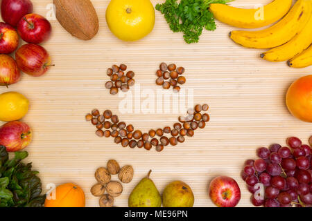 Flat lay of arranged hazelnuts in smile face surrounded with plenty of healthy fresh fruit and gree on wood. - Stock Image