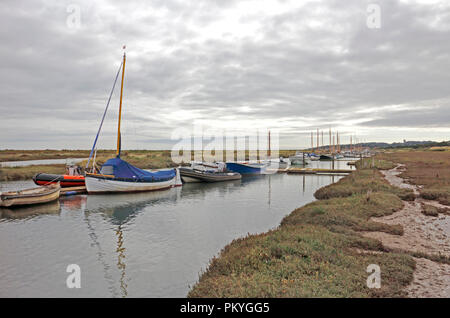 A view of a creek in salt marshes on the North Norfolk coast with moored boats at Morston, Norfolk, England, United Kingdom, Europe. - Stock Image