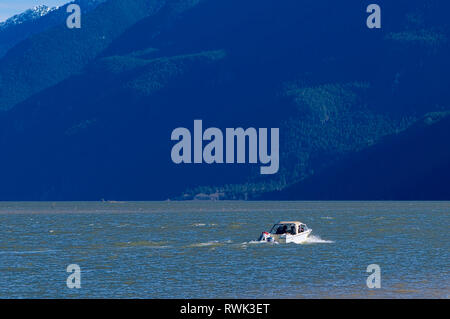 A single boat traveling on Pitt Lake with the dark side of a mountain looming in the background. Pitt Meadows, British Columbia, Canada - Stock Image