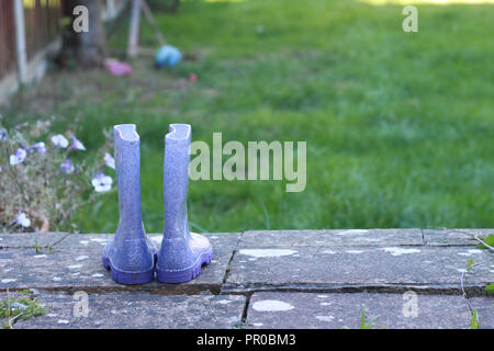 Child's purple welly boots on a step in a garden. - Stock Image