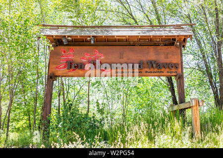 Santa Fe, USA - June 12, 2019: Sign for Ten Thousand Waves Japanese Health Spa entrance in New Mexico with green trees - Stock Image