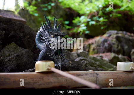 Dragon shaped water fountain at entrance of Towada Shinto shrine, in Aomori prefecture, North Japan. The fountain, called Temizuya, is used for a cere - Stock Image