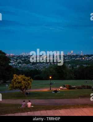 London, England, UK - June 1, 2019: Suburban streets and city skyline light up as viewed from Alexandra Palace Park in North London. - Stock Image