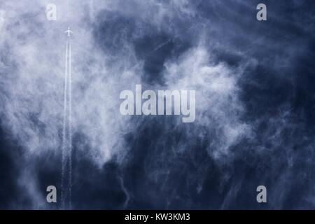 Far away jet plane travelling straight up with vapor trails against blue cloudy sky. - Stock Image