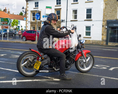 Elderly grey bearded motorcyclist on the custom built motorcycle he built himself, wafting to pull out into traffic - Stock Image