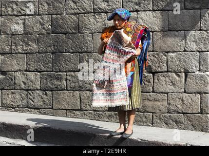 Isolated Guatemala Woman standing on Street Corner on Chichicastenango Market Day and selling Traditional Artisan Handicraft Textile and Carpets - Stock Image