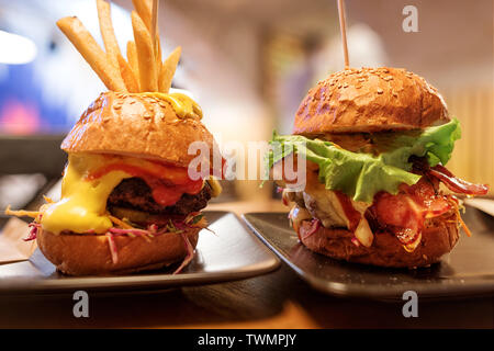 Two big tasty burger with ham and salad against defocused cafe background. Selective focus on the burger - Stock Image