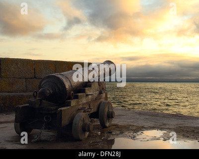 Old, rusted cannon pointing out to sea during a dramatic sunset over the sea. - Stock Image