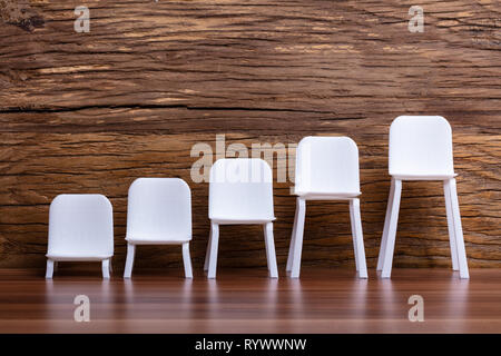 Empty Miniature Increasing Scale Of White Chair On Wooden Background - Stock Image