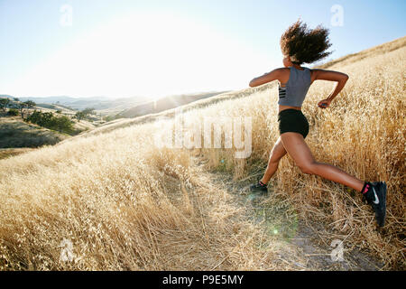 Young woman with curly brown hair running in urban park. - Stock Image