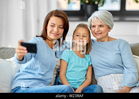 mother, daughter and grandmother taking selfie - Stock Image