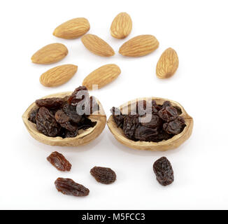 Shelled almonds and raisins with some raisins in two half almond shells - Stock Image