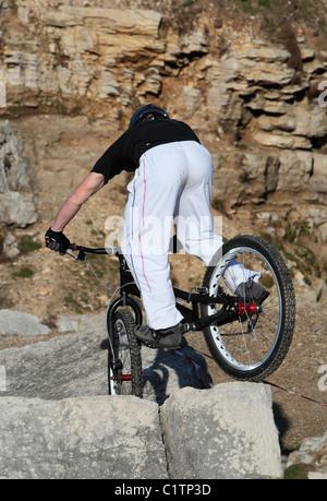 A young man on a mountain bike enjoys riding over some tough rocks - Stock Image