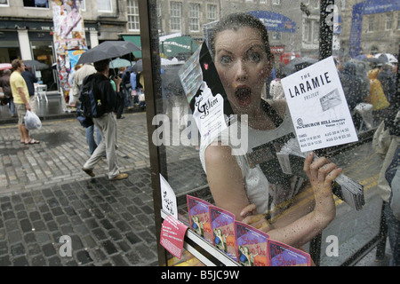 A Street Performer at the Edinburgh Fringe Festival on The Royal Mile A performer from Golden Prospects show shelters - Stock Image