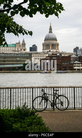 View of St Paul's cathedral from Southbank across the Thames with a bicycle chained to the rails, London, England. - Stock Image