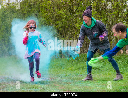 A young girl runner being covered in paint on Macmillan cancer charity 5K color fun run. - Stock Image