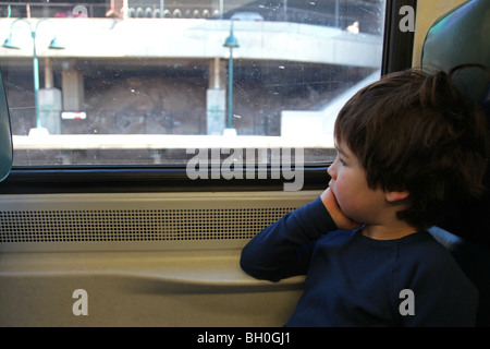 Boy gazing out the window of a commuter train - Stock Image