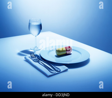 A dinning place setting with just an over sized capsule on the plate. - Stock Image