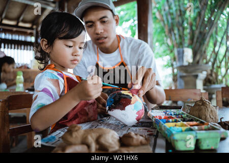 dad and daughter painting ceramic pot in pottery workshop together - Stock Image