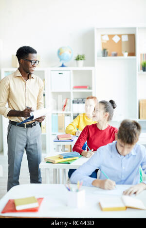 Happy teacher and schoolgirl looking at each other while discussing point concerning subject of lesson - Stock Image