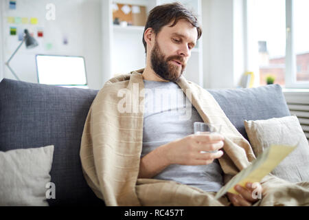 Bearded man with glass of water reading payment bill while sitting on sofa in living-room - Stock Image