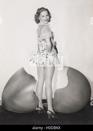 Woman standing by giant cracked egg shell - Stock Image