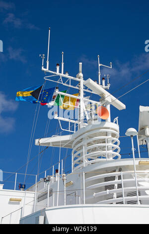 Navigation equipment and masts of cruise ship decorated with flags - Stock Image