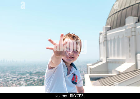 Young red haired boy laughing and reaching towards camera with Griffith Observatory and Los Angeles skyline behind him. - Stock Image