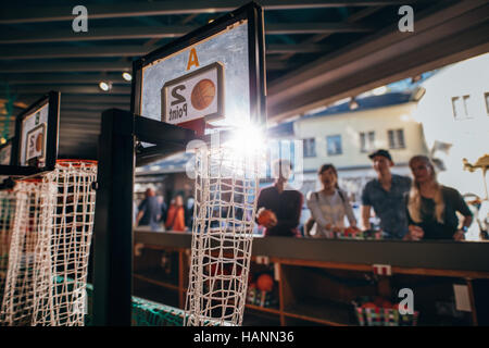 Group of friends shooting hoops at the fair. Focus on basketball hoop at amusement park stall. - Stock Image