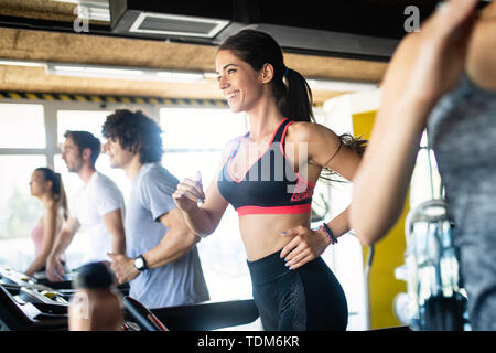 Happy fit people running on treadmill at fitness gym club - Stock Image