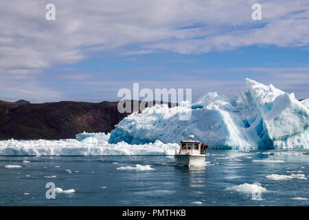 Tourists boat sailing in Tunulliarfik Fjord close to large icebergs from Qooroq icefjord in summer. Narsarsuaq, Kujalleq, Southern Greenland - Stock Image