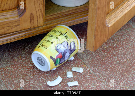 photographers coffee mug laying on tiled floor with broken handle after falling out of cupboard concept lack of focus - Stock Image