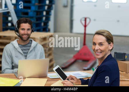 Portrait of warehouse managers using digital tablet and laptop - Stock Image