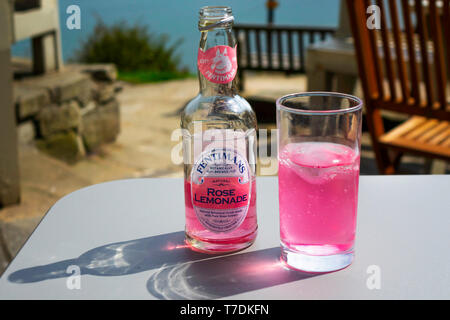 A glass and a bottle of cold Sparkling Fentimans Rose Lemonade on an outdoor table by the sea - Stock Image