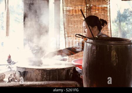 Vietnamese woman making rice paper in a rice paper factory - Stock Image