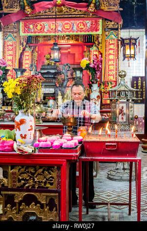 Sin Sze Si Ya Taoist Temple, Chinatown, Kuala Lumpur, Malaysia.  Worshiper Lighting Joss Sticks (incense Sticks).  Oldest Taoist temple in Kuala Lumpu - Stock Image