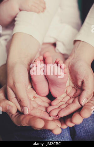 mom and dad are holding baby legs - Stock Image