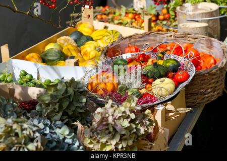 Autumn flowers and fruit are in various vessels and containers during the presentation of the harvest. - Stock Image