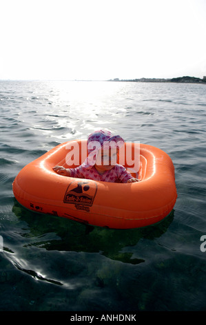 girl female toddler orange rubber ring sea cyprus holiday baby - Stock Image