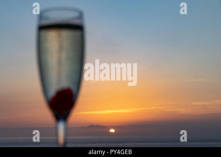 Bokeh image of evening celebrations as the sun sets over the Atlantic Ocean - Stock Image