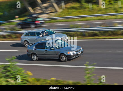 Two cars speeding along a motorway, one overtaking the other. Motion blur used to give a sense of speed. - Stock Image