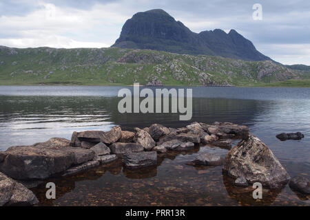 A view looking over Loch Fionn to Suilven Mountain, Lairg, Scotland with rocks in the foreground - Stock Image
