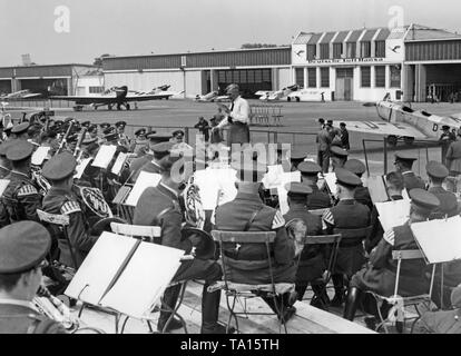 Preparations for the arrival of a zeppelin at Berlin Tempelhof Airport. A brass band on the maneuvering area in front of hangars of the Lufthansa. - Stock Image